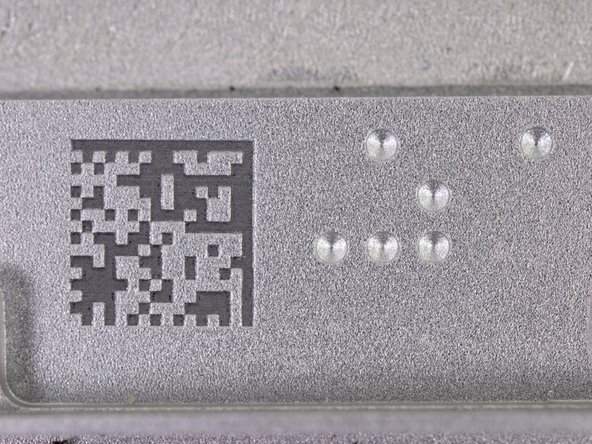 Image 2/2: The bottom edge of the case has two features that we found pretty neat: a ''laser engraved'' data matrix code and a nifty arrangement of round indentations.