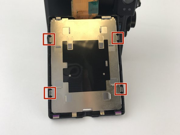 Once the two screws have been removed you must then locate the four prongs on the metal piece covering the back of the screen shown in the photo. Push each of these prongs in toward there parallel and pull up on the metal casing.