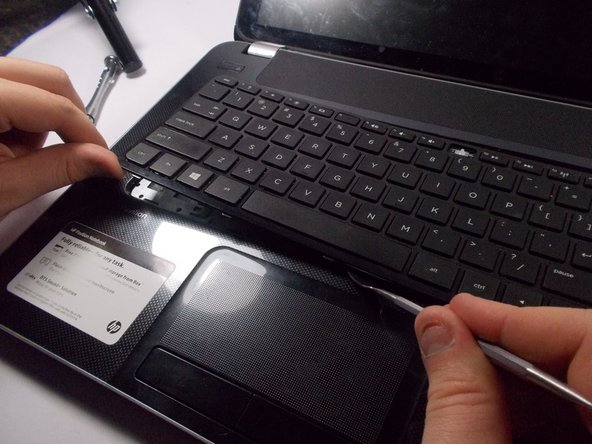 With a pair of tweezers or other thin object,  push in and slightly to the left (away from the disk drive compartment). On the face of the computer (the keyboard side), you will see part of the keyboard get pushed up. Using the spudger, wedge the keyboard and slide the spudger along all four corners.