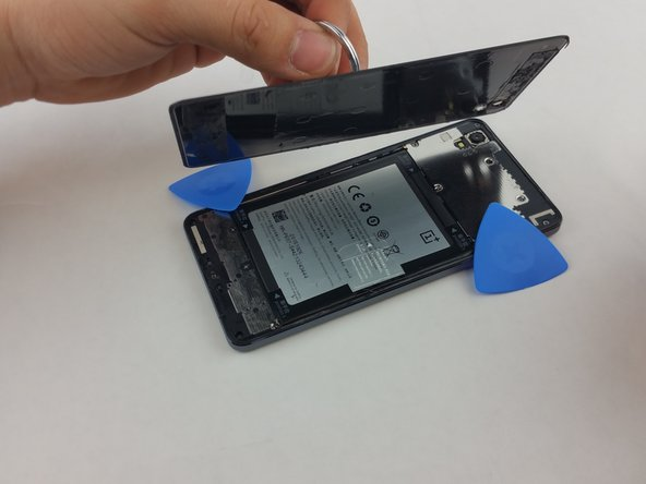 Image 2/3: Use the suction cup to safely remove the panel from the device. As you work around the panel's edges, the lingering heat may cause the remaining adhesive to reattach the panel to the device.