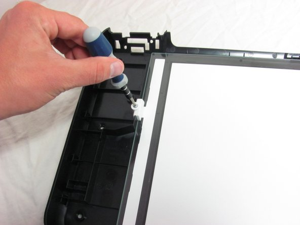 With the glass facing upwards, remove the screw holding the glass in place.