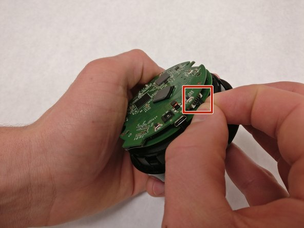 Detach the white plug by gently pulling on the black wires.