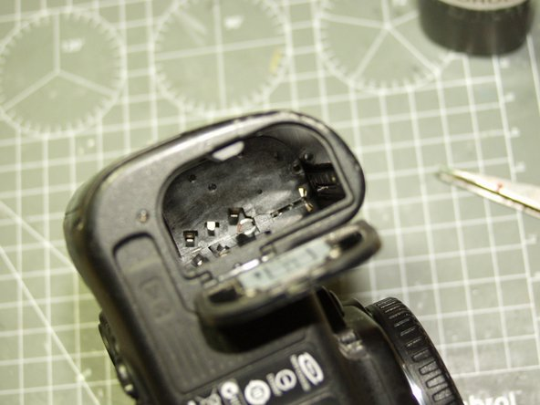 The grip is attached to the body via a tab which is fastened by a small screw, that is accessible from the battery compartment. Remove the battery, you can see it in the photo upper right towards the front of the camera. unscrew this and keep the screw safe.