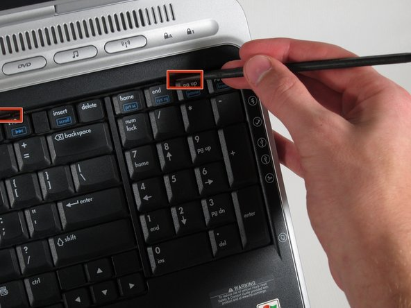 Push up on the four latches located at the top of the keyboard with the spudger to release them.