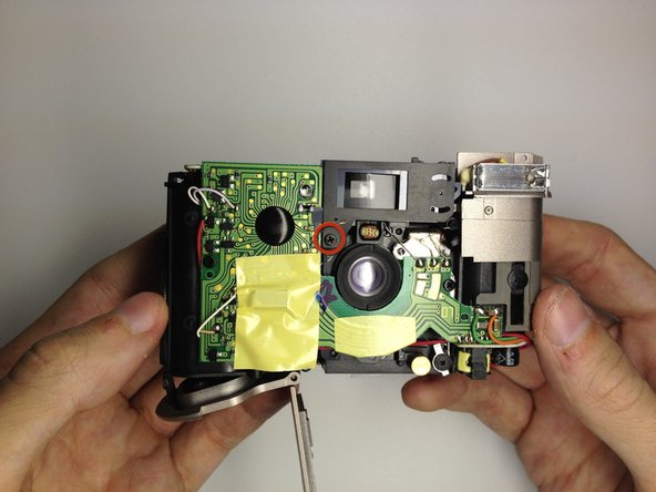 Locate the screw on the front of the camera that holds the view finder assembly.