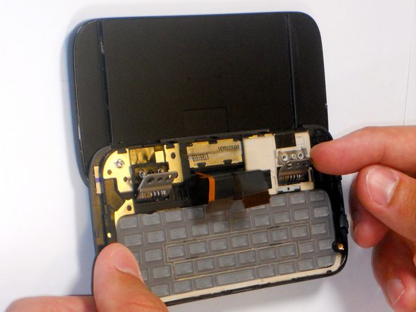 Image 1/2: Carefully lift keyboard frame away from display screen.