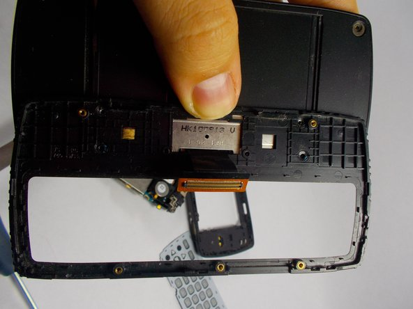 Image 1/2: Flip phone over, and notice where the camera lies on the other side, there are three small clips connecting a black casing over the section of the phone. Gently using your hands or the prying tool, take these clips off.