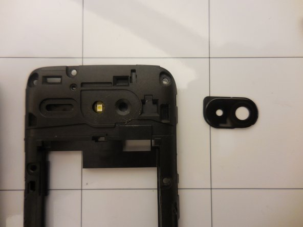 Use the spudger to pry the camera lens and remove it from the rear frame.  Then you can replace the lens.