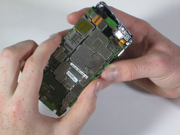 Use your fingers to gently pull the motherboard down and out of the rear casing.
