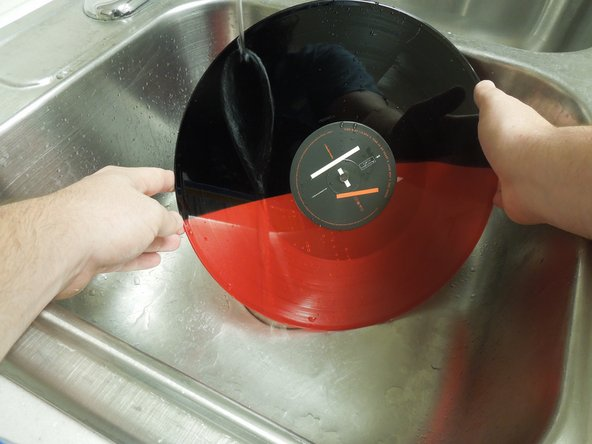 Put the LP record in the sink and run cold water over the LP record.