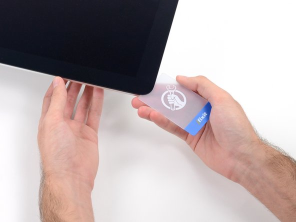 Insert a second plastic card into the gap between the display and frame located at the top left corner of the iMac.