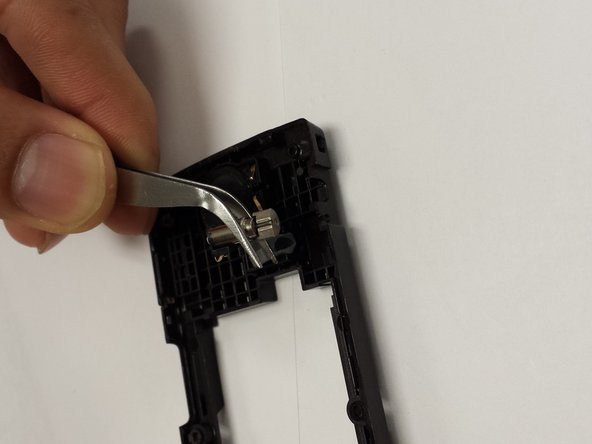 The antenna is located on the opposite side of the black plastic cover.  Use the tweezers to remove the antenna.