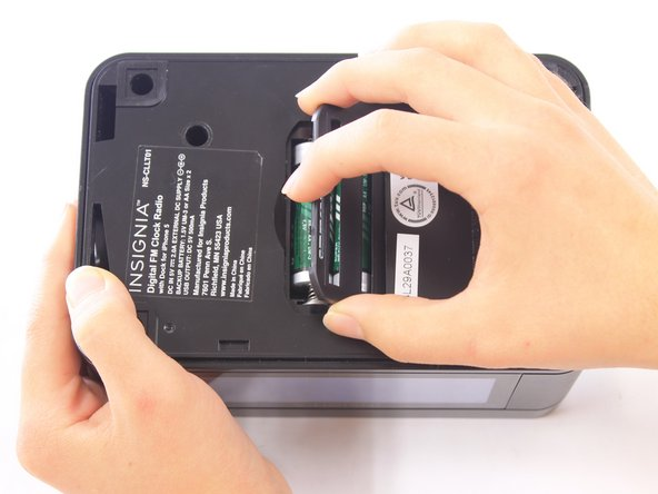 Image 2/3: Lift the battery cover up and to the right to reveal the batteries.