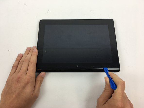 Flip the tablet over and use a plastic opening tool to pry the casing away from the top of the screen. Push the back cover off.