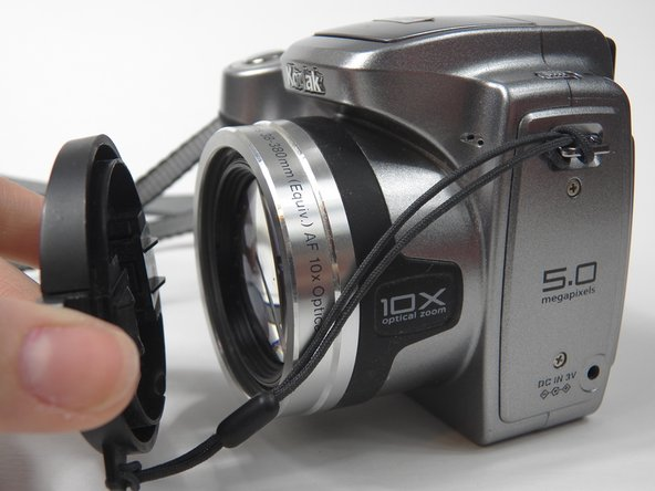 Remove lens cover from the camera by squeezing the protruding button on each side of the cover and pulling.