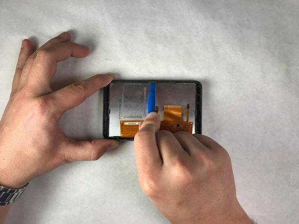 Use a plastic opening tool to loosen the three clips located on the top of the screen encasing to a position that loosens the hold on the screen.