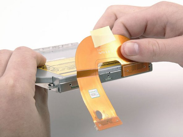 Image 1/1: Peel the cable up from the top of the optical drive, removing tape as necessary, and disconnect it.