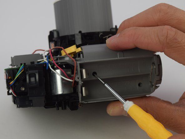 Remove the four 4.5 mm screws inside the battery  holder with a long #00 Phillips screwdriver.