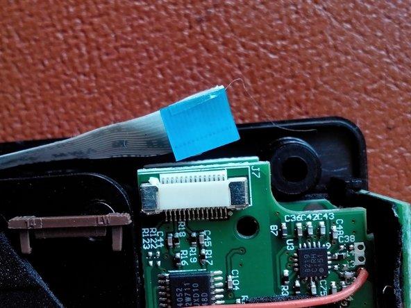 Der breite am linken Geräterand wird mit einer braunen Klammer gehalten, die einfach herausgezogen werden kann. Danach ist das Flachkabel direkt lose.