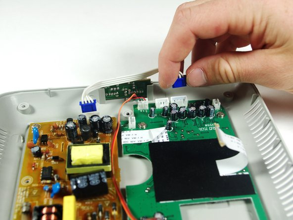Image 3/3: Pull the white cable with the blue adapters off of the circuit boards.