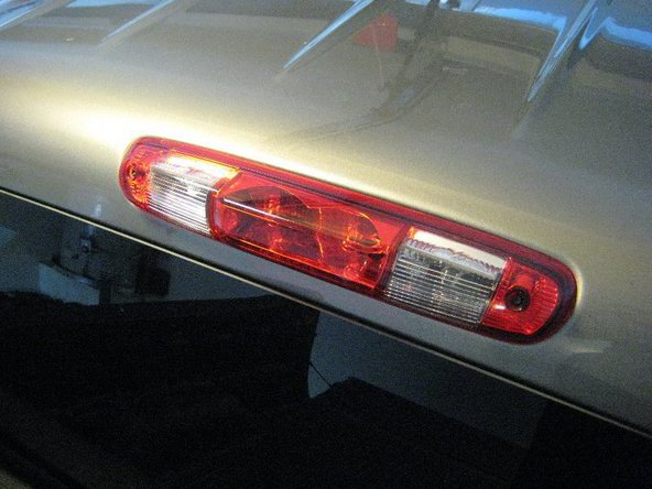 Take the Philips screwdriver and remove two Philips head screws on both sides of the high mount brake lamp.