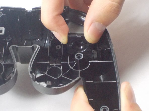 Finally remove the screws holding in the right and left triggers. It's easiest to hold the trigger together as shown in the third picture. Remove both the left and right trigger, and then you have successfully removed your back panel.