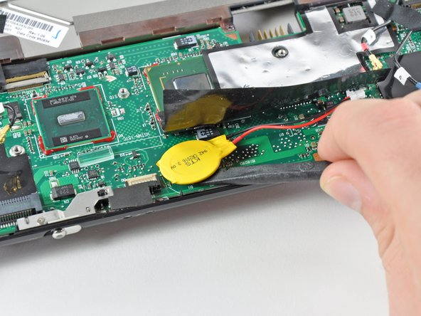 Image 2/2: Use the flat end of a spudger to pry the PRAM battery off the adhesive securing it to the motherboard.