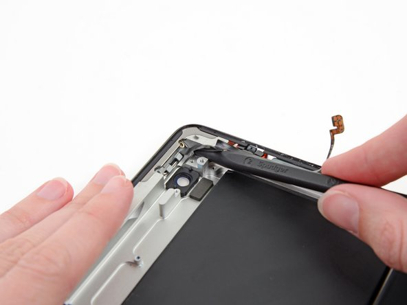 Image 3/3: With the tip of the spudger still underneath the ribbon cable, gently lift the power button out of its socket in the aluminum frame.