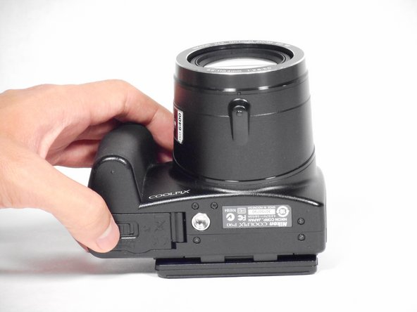 Use your finger to push the notch of the compartment door to the center of the camera body.