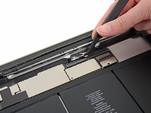 Use a pair of tweezers to peel back the piece of tape that secures the digitizer ribbon cable to the logic board.