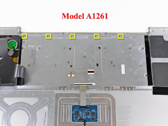 The keyboard on A1261 models has five locking tabs. Their locations are shown in the second picture.
