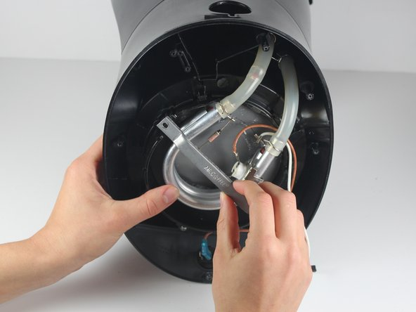 Gently lift the silver support bracket to free the heating plate from the heating coil.