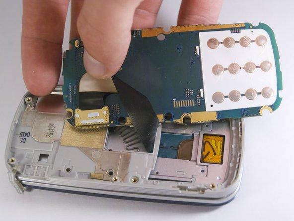 Saisissez la carte mère et tirez doucement pour la séparer du reste du téléphone.