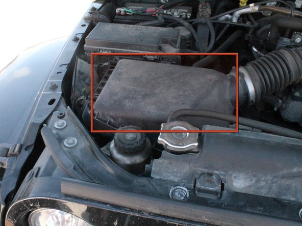 Locate the air filter box in front of the car battery.  It will have a 4-inch diameter hose coming out of one side (towards the center of the vehicle) and an air release coming out of the other side.  It should have four clamps keeping it sealed.