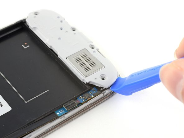 Use an opening tool to unclip the speaker assembly on the bottom of the phone.