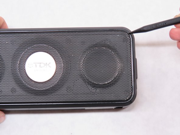 Image 1/3: Stick the point of the spudger into one of the corners surrounding the faceplate and gently pull it up.