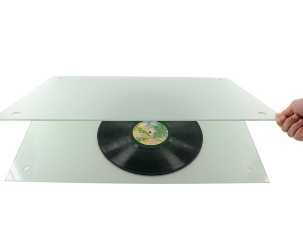 Gently set the second glass panel on top of the record.