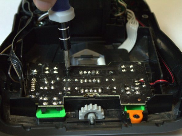 Remove the eight black 7.2 mm Phillips #0 screws from the top of the circuit board and remove the circuit board.