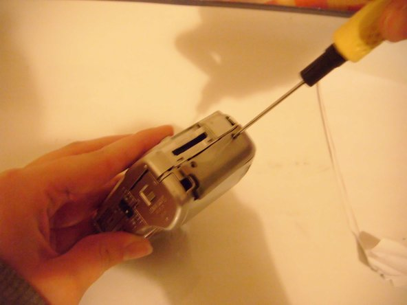 Use a small Philips screwdriver to remove the two screws from the side of the camera where the card reader is.