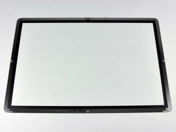 Image 3/3: The rear of the glass has a metallic bezel, as well as seven alignment posts. The magnets that help hold the glass in place are in the iMac's aluminum front bezel.