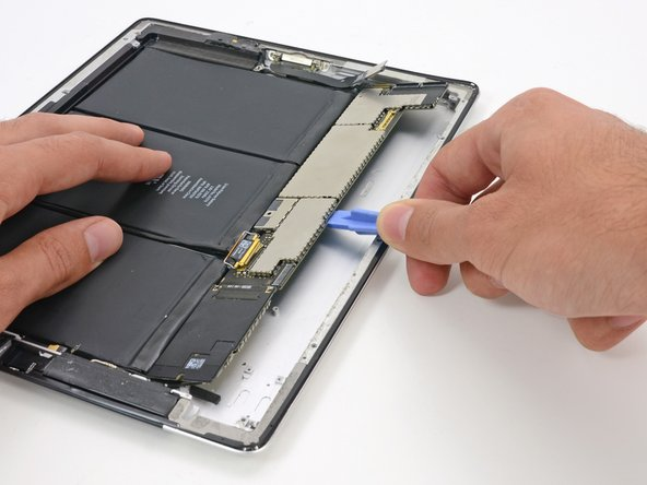 The logic board is adhered to the rear case; work slowly and uniformly to peel up the glue without damaging the board.
