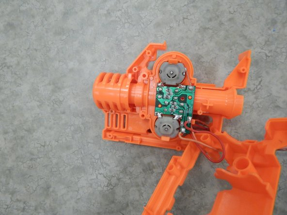 With the shell now removed, locate the motor and controlling circuit board. With your index finger and thumb, squeeze the holders shown in Figure 2 and pull upwards to release the motor module from the rest of the motor's casing. Your motor should be detached from the casing, as shown in Figure 3.