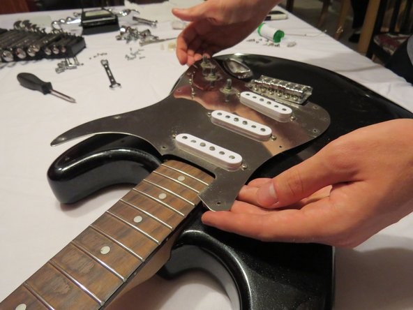 Image 1/3: Carefully rotate the pickguard away from the guitar. Notice the electronics. There is a wire that runs through the body to the output jack.