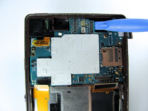 Image 1/3: Firmly lift the section up where the silver part of the motherboard comes to the edge of the green base board.