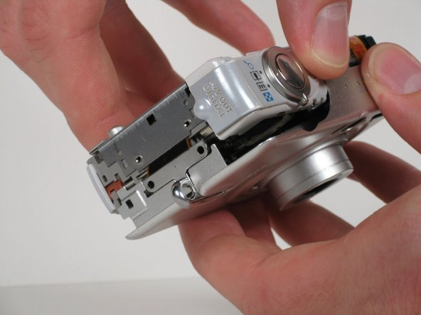 Use your fingers to carefully pry off the front casing of the camera. The front casing should pull straight off.