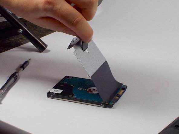 Pull up on the black Mylar sheet and remove it from the existing hard drive, it has some adhesive, but will simply pull off with just a small amount of force.