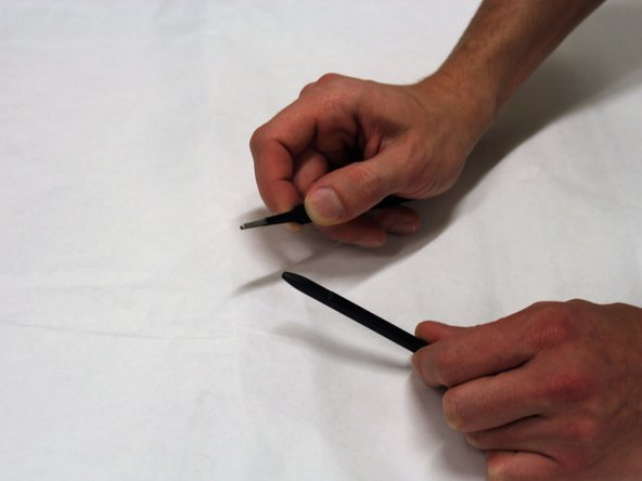 Pinch the two ends of the tweezers together so that the tip of the stylus is firmly clasped while pulling it away from the barrel.