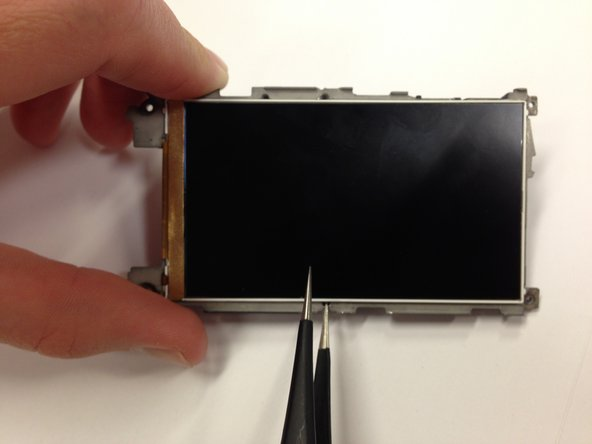Slide the tweezers underneath the LCD, around the three silver edges, until the entire display is lifted from grey plastic.