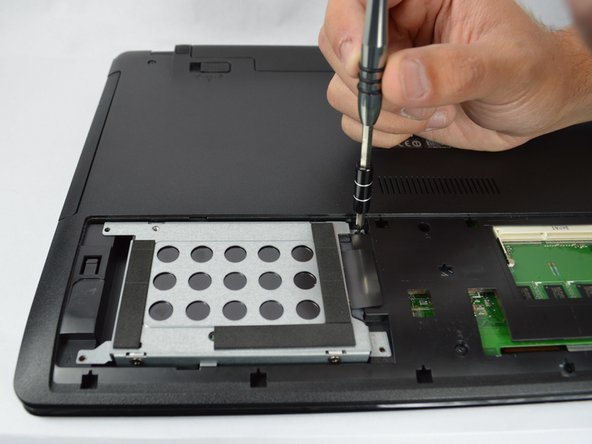 Remove the three 5mm screws holding down the hard drive and the five 5mm screws holding down the casing using a Phillips #00 bit.