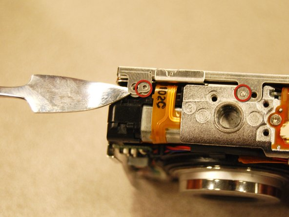 Image 1/3: First, use a spudger to pry the the two tabs from the small guide pins.